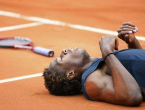 France's Gael Monfils lies on the court during his semi-final match against Switzerland's Roger Federer at the French Open tennis tournament at Roland Garros in Paris