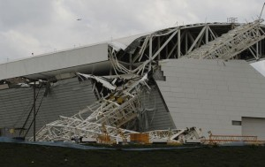 "Workers stand near a crane that collapsed on the site of the Arena Sao Paulo stadium, known as ""Itaquerao"", which will host the opening soccer match of the 2014 World Cup, in Sao Paulo"