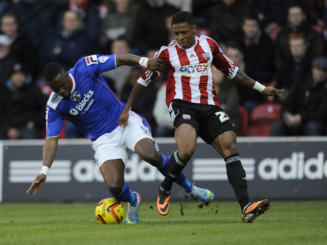 LONDON, ENGLAND - DECEMBER 14: Genseric Kusunga of Oldham Athletic is tackled by Kadeem Harris of Brentford during the Sky Bet League One match between Brentford and Oldham Athletic at Griffin Park on December 14, 2013 in London, England. (Photo by Rob Munro/Getty Images)
