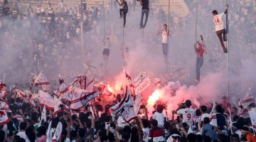 In this July 31, 2015 photo, Zamalek soccer fans celebrate after winning the Egyptian League at the Zamalek Sports Club, in the Air Defense Stadium in Cairo, Egypt. The hardcore fan base Ultras White Knights did not celebrate the winning of the team out of respect for more than 20 soccer fans who were crushed to death outside the Air Defense Stadium in Cairo after police fired tear gas to break up the crowd waiting in a fenced, narrow corridor to watch. Police accused the fans of attacking the force, and rioting to enter the stadium on Feb. 8, 2015. (AP Photo/Mohammed El Raai)