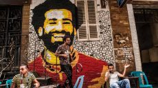 """Ahmed Fathy (C), a 26-year-old Egyptian artist, descends a small staircase at an open-air cafe in downtown Cairo on April 30, 2018 past a mural he painted depicting the smiling face of Liverpool's Egyptian midfielder Mohamed Salah. Patriotic statements, flashy commercials, and an anti-drug campaign: as Liverpool winger Mohamed Salah takes the football world by storm, Salah is put under the spotlight in Egypt as a global figure. Salah, the """"Pharaoh"""" represents an opportunity for the country to improve its image internationally after years of security, political, and economic turmoil in the aftermath of the 2011 uprising that toppled longtime ruler Hosni Mubarak. / AFP / KHALED DESOUKI"""
