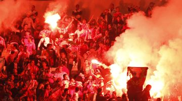 Fans of Morocco's Wydad Casablanca light flares as they watch their team's African Champions League final soccer match against Tunisia's Esperance Sportive de Tunis, in Tunis November 12, 2011.   REUTERS/Zoubeir Souissi   (TUNISIA - Tags: SPORT SOCCER)